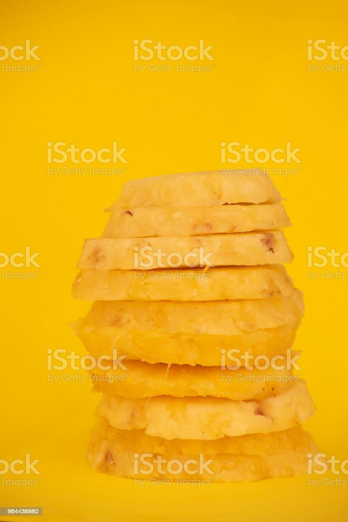 Circles cut peeled pineapple slices on yellow background - Royalty-free Bright Stock Photo