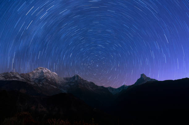 Circling stars and mountain Cicling stars and annapurna mountain region in night north star stock pictures, royalty-free photos & images