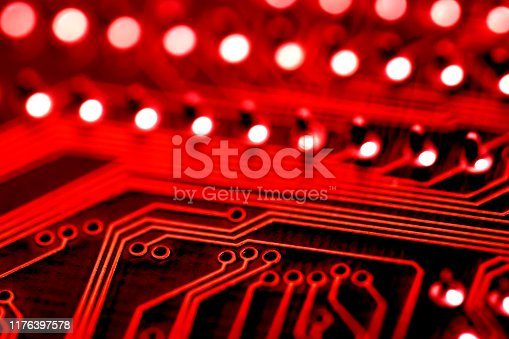 Close-up photo of an electronic circuit board in red tones. Shallow depth of field, beautiful bokeh.
