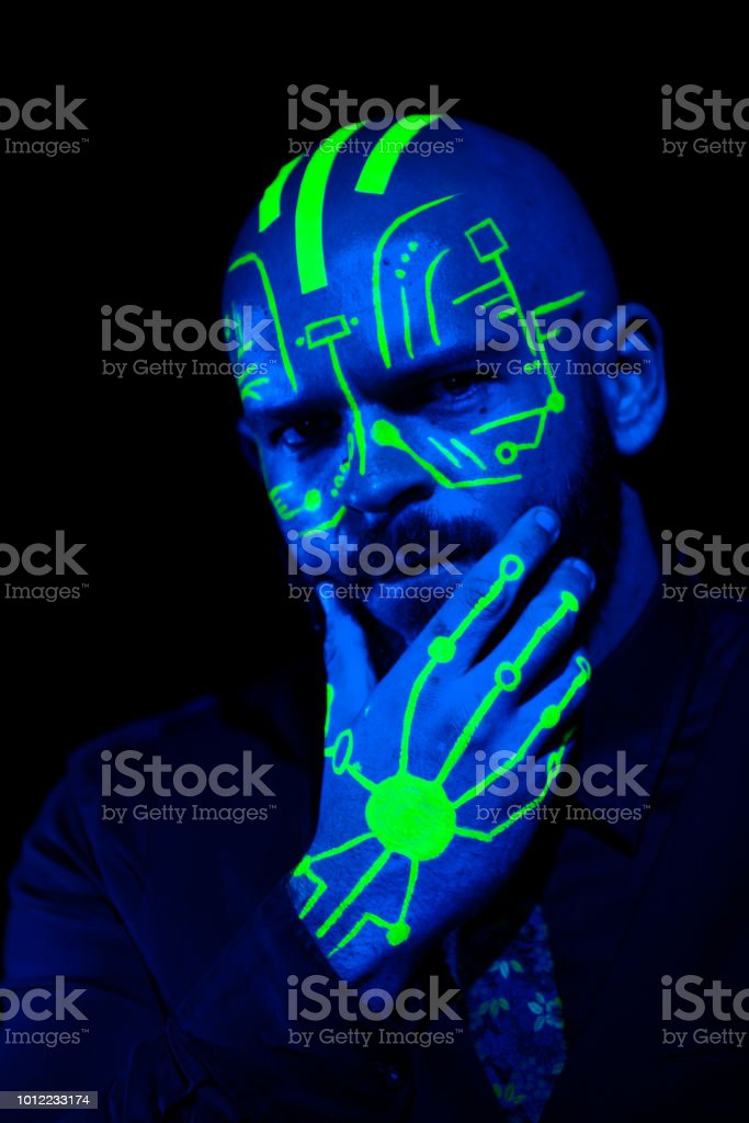 A caucasian male model with green blacklight paint. Paint resembles a...