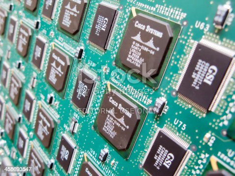 Amsterdam, The Netherlands - June 26, 2009: Circuit board close up, electronic components mounted on green cuircuit board.