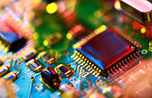 Abstract electronic circuit board in multi-colored lighting, close-up.