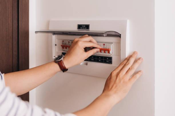 circuit breaker board toont veel schakelingen. een vinger staat op het punt om hem weer aan te zetten - elektrische fitting stockfoto's en -beelden