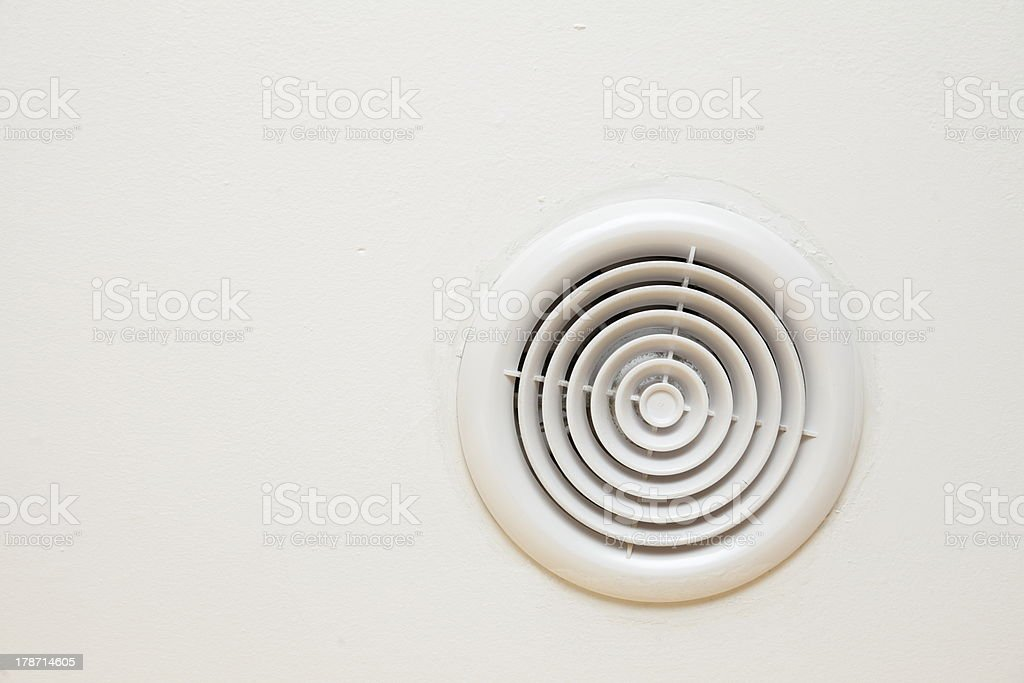 circular plastic air vent in white wall stock photo