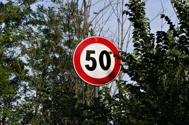 circular road sign limiting the speed to 50 kilometers per hour (pesaro, italy, europe) - cartello stradale italia km foto e immagini stock