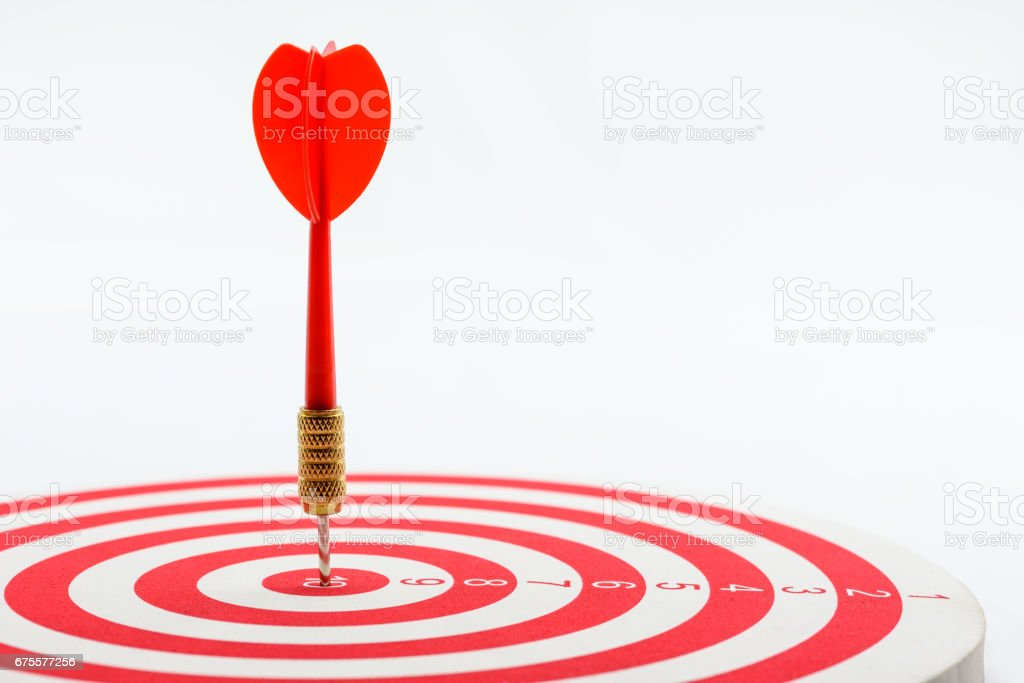 Circular target marked with numbers and red dart. stock photo