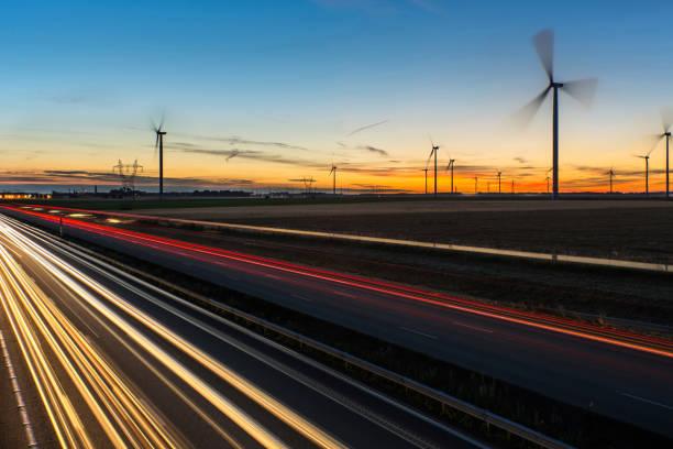 Circulation dense sur l'autoroute au lever du soleil vue sur l'autoroute A1 au lever du soleil avec un champs d'éoliennes picardy stock pictures, royalty-free photos & images