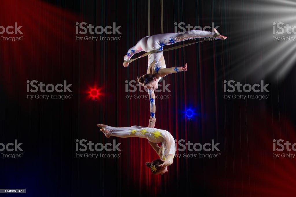 馬戲團女演員雜技表演。兩個女孩在空中表演雜技。 - 免版稅人圖庫照片