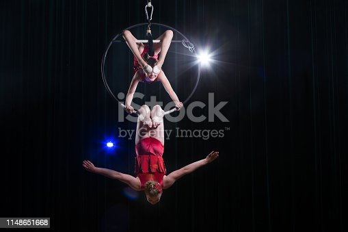 istock Circus actress acrobat performance. Two girls perform acrobatic elements in the air ring. 1148651668