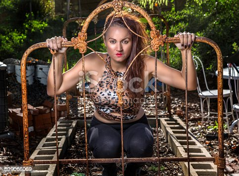 A beautiful Circus performer posing on a vintage bed post.