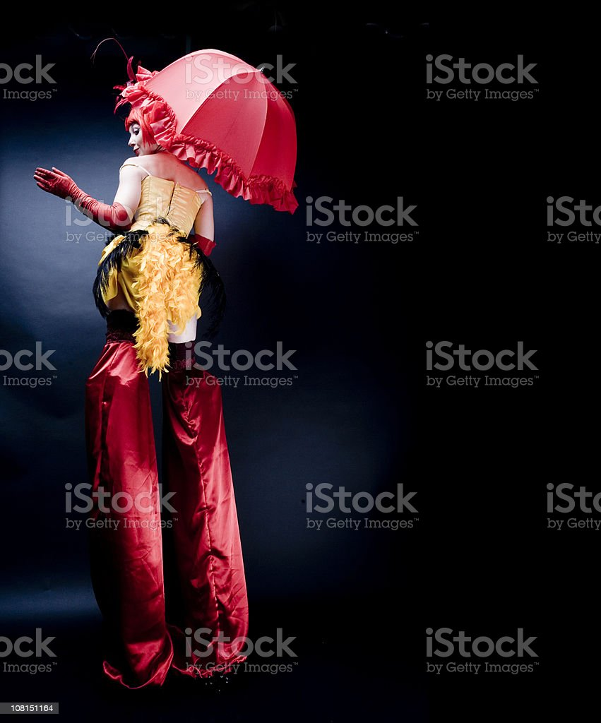 Circus Performer in Costume Wearing Stilts, Low Key royalty-free stock photo