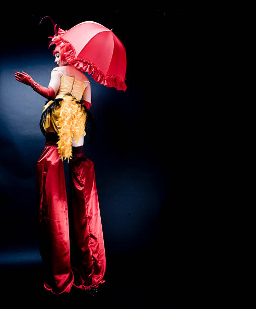 Circus Performer in Costume Wearing Stilts, Low Key stock photo