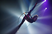 Young woman performing acrobatic element on aerial ring indoors, air stretch, splits in air