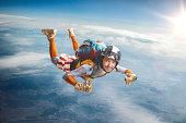 Circus skydiver falls through the air. Thumbs up!