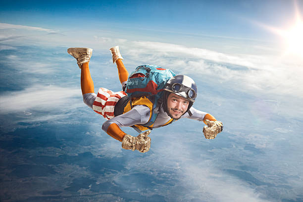 Circus skydiver falls through the air. Circus skydiver falls through the air. Thumbs up! parachuting stock pictures, royalty-free photos & images