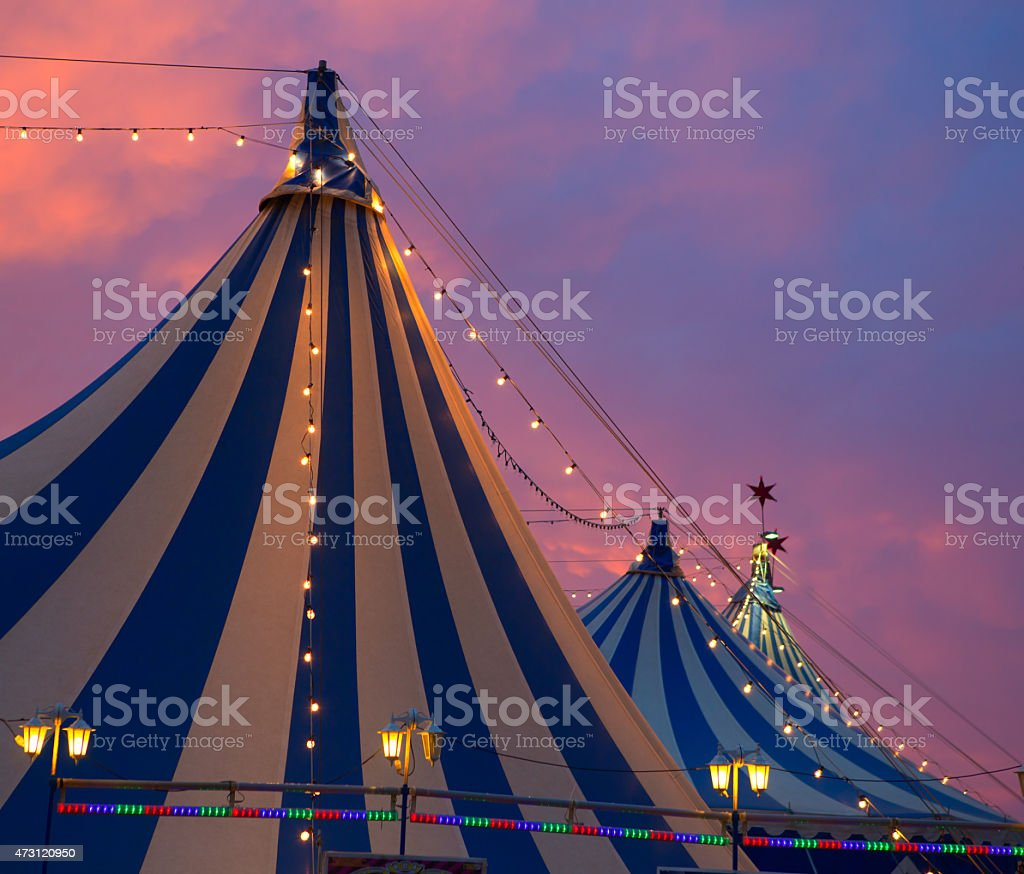 Circus tents illuminated by string lights against sunset stock photo