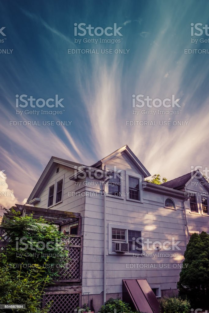 Cirrus Clouds Emerging Behind A House stock photo