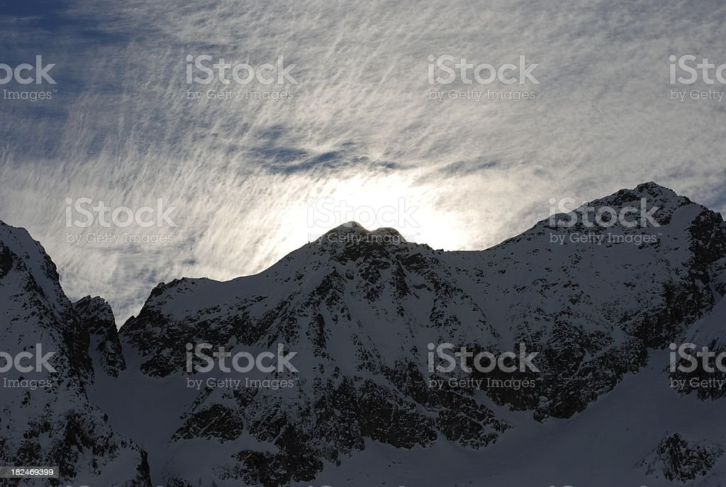 Cirrus clouds over the snow-capped mountains stock photo
