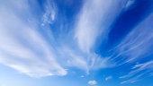 High white wispy cirrus clouds with cirri-stratus in the blue sky