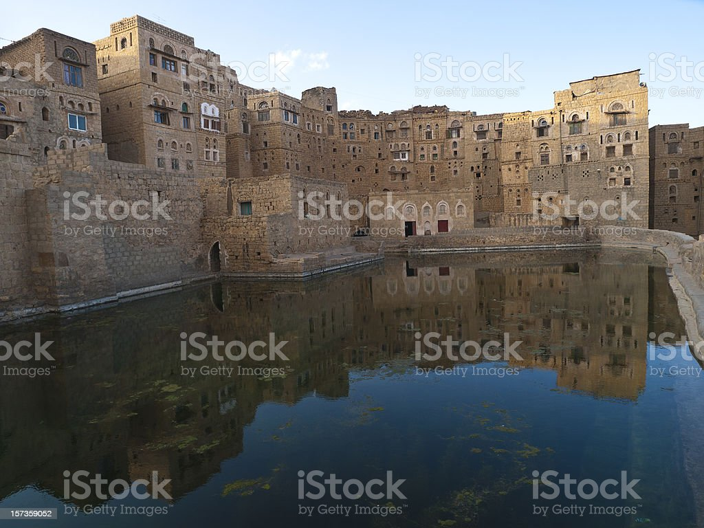 A cistern in Hababa, Yemen reflecting the surrounding houses stock photo