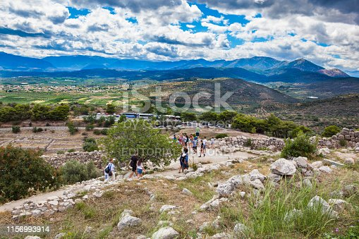 Mycenae, Greece - June 28, 2018: The citadel of Mycenae is an archaeological site dating from the 16th to the 12th century BC. On this photography, you can see people walking on the site and the parking area with buses and cars.