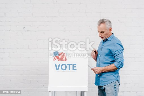 istock citizen holding pen while looking at ballot near voting stand 1202730384