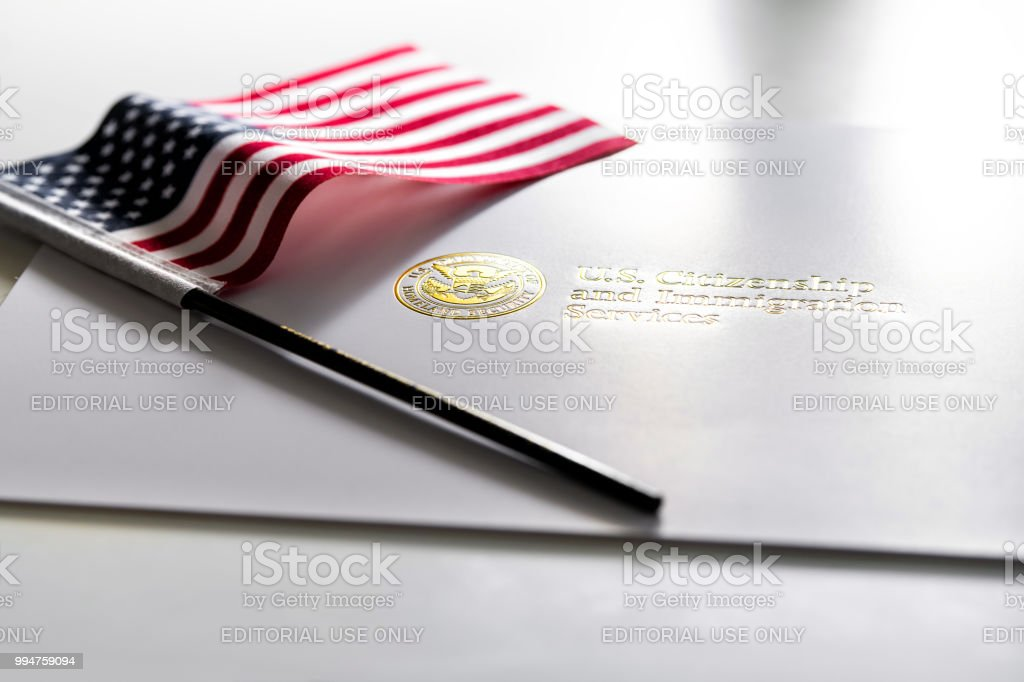 U.S. Citizenship and Immigration Services envelope, white folder for naturalization certificate on table with American flag stock photo