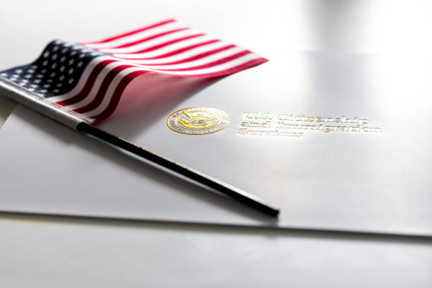 U.S. Citizenship and Immigration Services envelope, white folder for naturalization certificate on table with American flag Fairfax, USA - April 11, 2018: U.S. Citizenship and Immigration Services envelope, white folder for naturalization certificate on table with American flag department of homeland security stock pictures, royalty-free photos & images