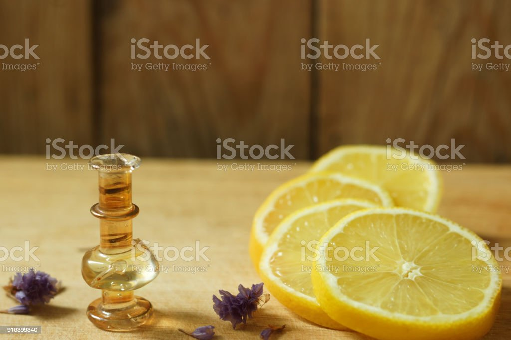 Citric acid in a bottle on a wooden table, next to a lemon, sliced slices stock photo
