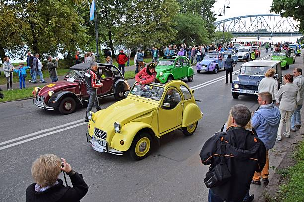 Citroen 2CV vehicles driving on the street during the parade - Photo
