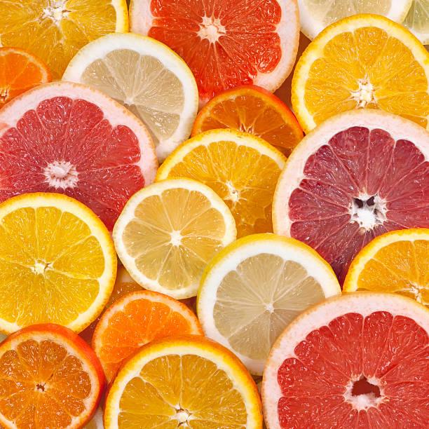 Citrus background Closeup of sliced citrus fruits background citrus fruit stock pictures, royalty-free photos & images