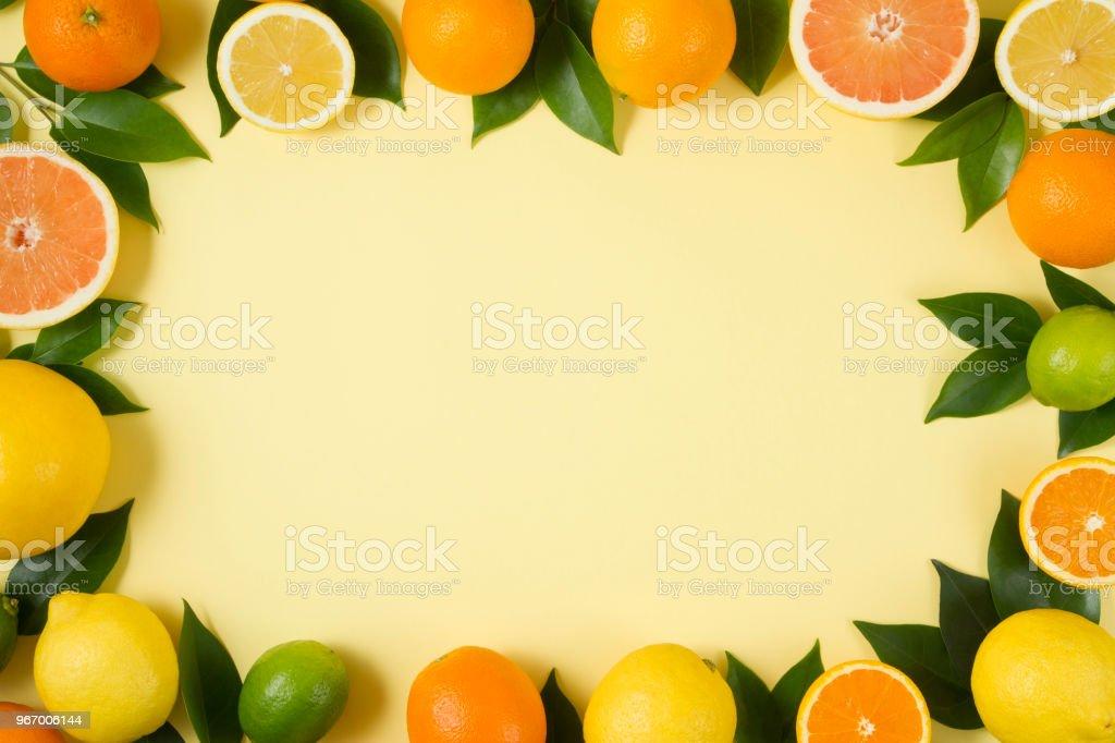 Tropical fruits, lemon, orange, grape fruits and green leaves on soft...