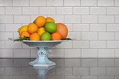 Homegrown selection of citrus fruit in retro modern kitchen with white ceramic subway tile backsplash and quartz countertop.