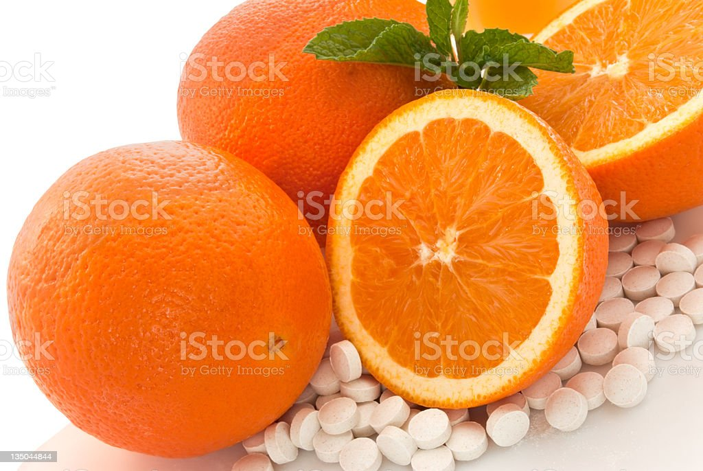 Citrus Fruit Oranges with Vitamin C pills and green garnish royalty-free stock photo