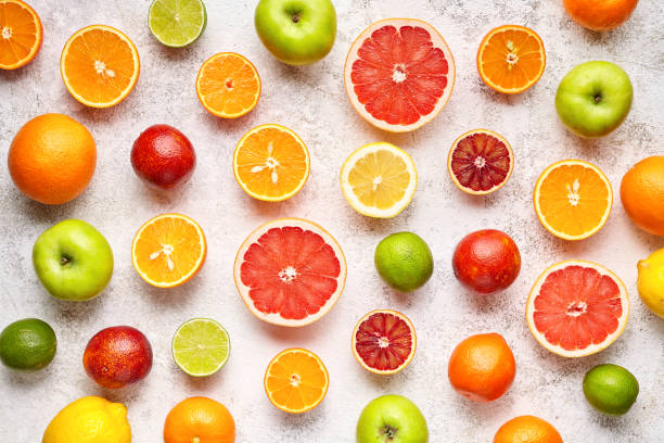 Citrus fruit pattern on white concrete table. Food background. Healthy eating. Antioxidant, detox, dieting, clean eating, vegetarian, vegan, fitness or healthy lifestyle concept stock photo