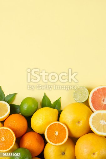 tropical fruits, lemon, orange, grape fruits and green leaves on yellow paper background