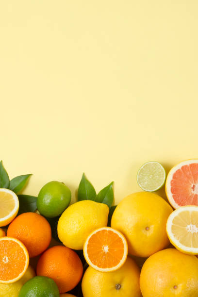 citrus fruits and green leaves on yellow background - agrume foto e immagini stock