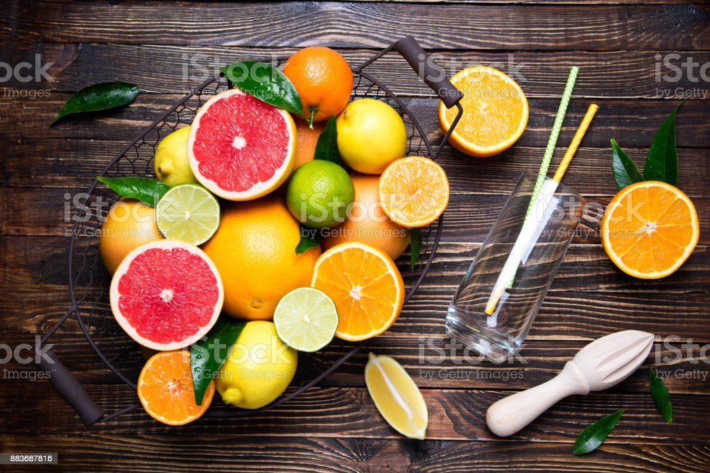 Citrus fruits background. Assorted fresh citrus fruits with leaves....