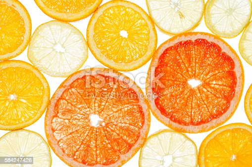 Lemon, grapefruit and orange cut by segments located close photographed against the light isolated on white background