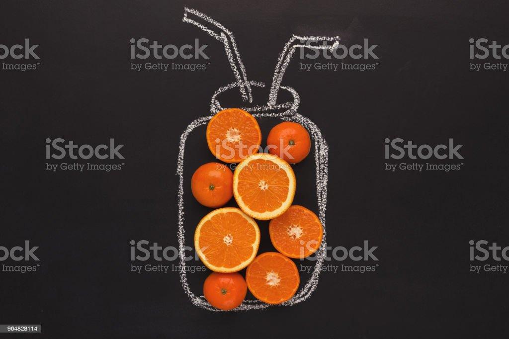Citrus fruits in chalk drawn jar on black background royalty-free stock photo
