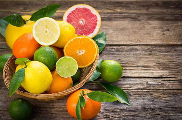 citrus obst im korb auf rustikalen tisch - zitrusfrucht stock-fotos und bilder