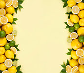Lemon, orange, grape fruits and green leaves on soft yellow paper background