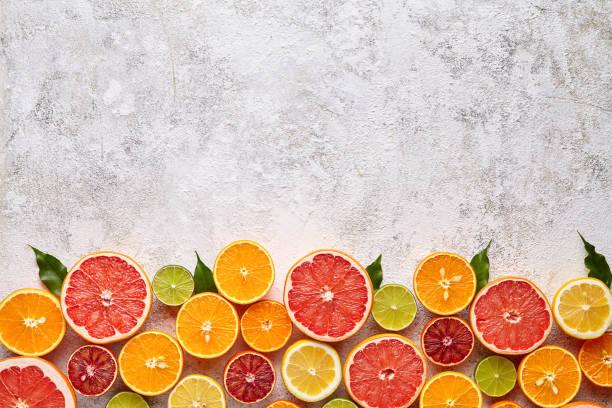 Citrus fruits vegan mix flat lay on white background, helthy vegetarian organic food stock photo
