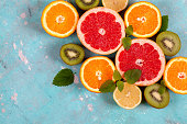 Fresh Citrus fruits with orange, lemon, grapefruit and kiwi fruit with mint on blue concrete background. Flat lay image, Space for text.