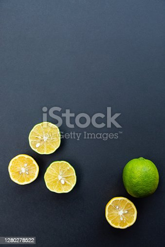 Citrus. Lemons and limes whole and halves on a black background. Healthy food and vitamins
