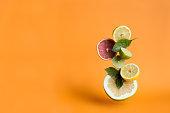 Levitating orange, lime and lemon with basil leaves on the orange background. Citrus
