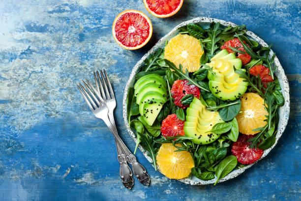 Zitrus-Salat mit gemischten Grünen und Blutorange. Vegan, vegetarisch, sauber Essen, Diäten, Food-Konzept. Blauer Stein Hintergrund. – Foto