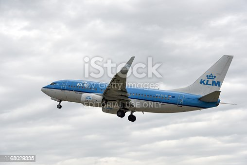 KLM Cittyhopper during take off procedure at Airport Zurich. The Boing 737 Aircraft leavs to cloudy sky.