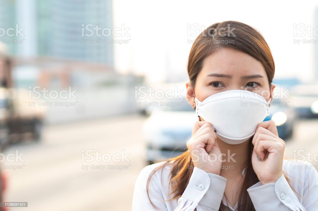City air pollution concept. Close up woman wearing N95 mask to...