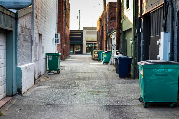 City alley with trash, dumpsters, and garbage cans stock photo
